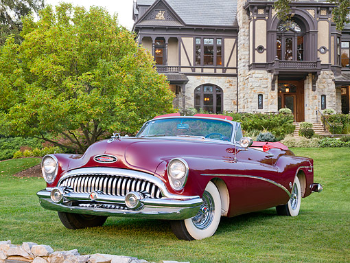 AUT 21 RK3195 01 © Kimball Stock 1953 Buick Skylark Convertible Red 3/4 Front View On Grass By Trees And House