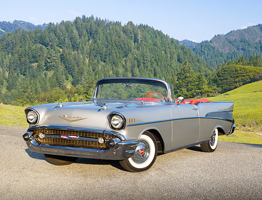 AUT 21 RK3206 01 © Kimball Stock 1957 Chevrolet Bel Air Convertible Silver 3/4 Front View On Pavement By Evergreen Trees