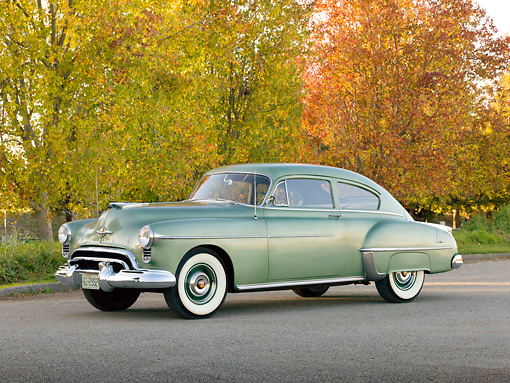 AUT 21 RK3209 01 © Kimball Stock 1950 Oldsmobile Futuramic 88 Club Sedan Moss Green 3/4 Front View On Pavement By Autumn Trees