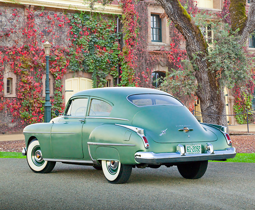 AUT 21 RK3212 01 © Kimball Stock 1950 Oldsmobile Futuramic 88 Club Sedan Moss Green 3/4 Rear View On Pavement By Ivy Covered Building