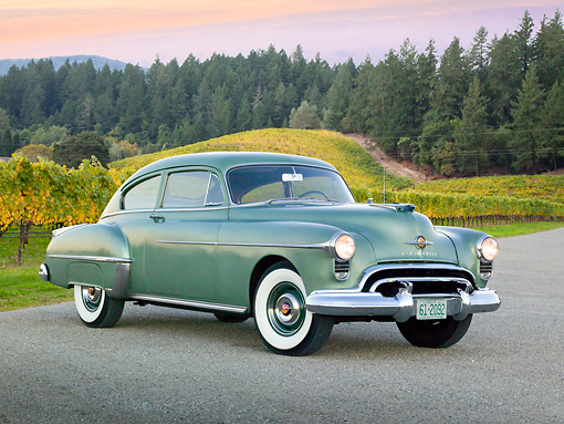 AUT 21 RK3214 01 © Kimball Stock 1950 Oldsmobile Futuramic 88 Club Sedan Moss Green 3/4 Front View On Pavement By Vineyard And Evergreen Trees