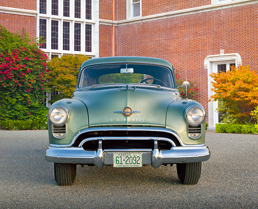 AUT 21 RK3218 01 © Kimball Stock 1950 Oldsmobile Futuramic 88 Club Sedan Moss Green Front View On Pavement By Brick Building