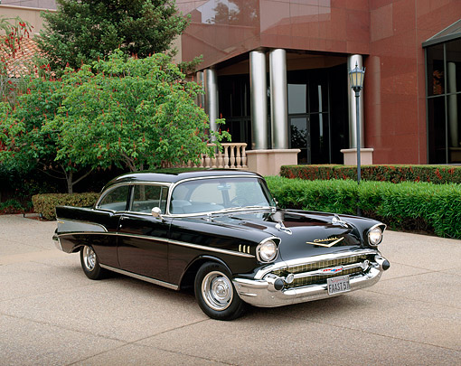AUT 21 RK3222 01 © Kimball Stock 1957 Chevrolet Bel Air Black 3/4 Front View On Pavement By Building