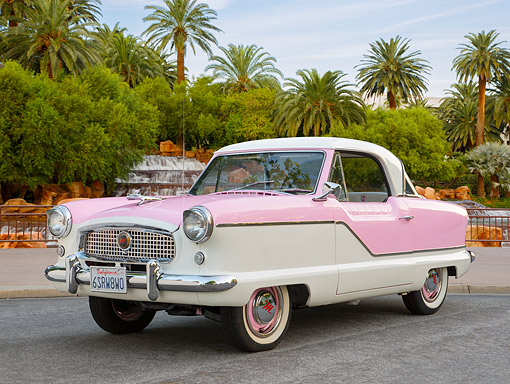 AUT 21 RK3229 01 © Kimball Stock 1958 Nash Metropolitan Series III Coupe Pink And White 3/4 Front View On Pavement By Palm Trees