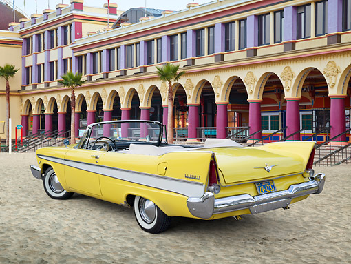 AUT 21 RK3233 01 © Kimball Stock 1957 Plymouth Belvedere Convertible Canary Yellow 3/4 Rear View On Sand By Boardwalk