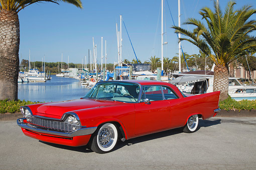 AUT 21 RK3235 01 © Kimball Stock 1958 Chrysler Windsor Red 3/4 Front View On Pavement By Sailboats