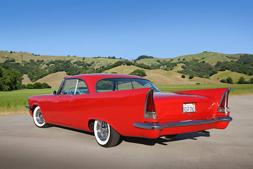 AUT 21 RK3240 01 © Kimball Stock 1958 Chrysler Windsor Red 3/4 Rear View On Pavement By Grassy Hills