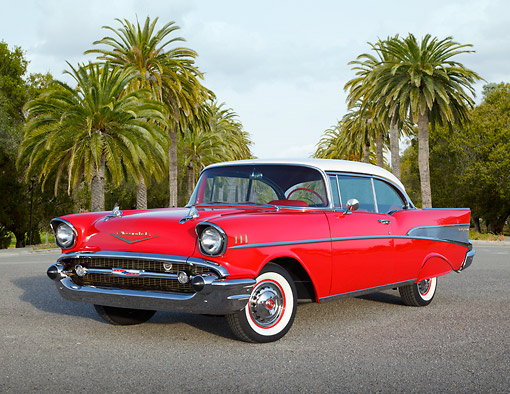 AUT 21 RK3249 01 © Kimball Stock 1957 Chevrolet Bel Air Red With White Top 3/4 Front View On Pavement By Palm Trees