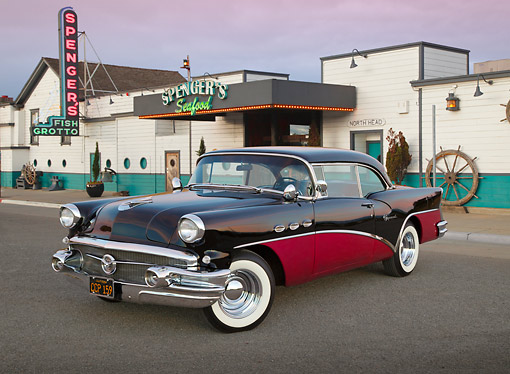 AUT 21 RK3266 01 © Kimball Stock 1956 Buick Special Black And Fuschia 3/4 Front View On Pavement By Restaurant At Dusk