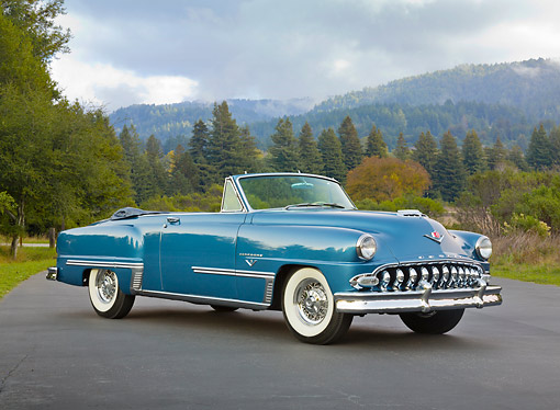 AUT 21 RK3278 01 © Kimball Stock 1953 DeSoto Firedome French Blue 3/4 Front View On Pavement By Evergreen Trees And Hills