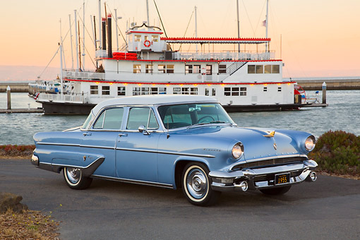AUT 21 RK3282 01 © Kimball Stock 1955 Lincoln Capri Blue and White 3/4 Side View On Pavement By Boat At Dusk