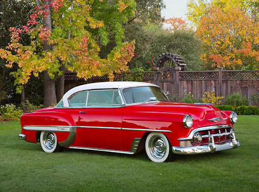 AUT 21 RK3288 01 © Kimball Stock 1953 Chevrolet Bel Air Torch Red 3/4 Front View On Grass By Fence And Autumn Trees
