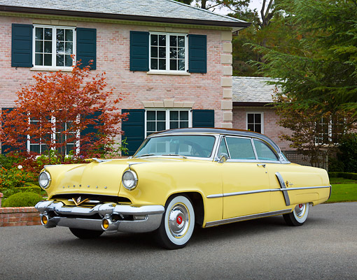 AUT 21 RK3293 01 © Kimball Stock 1953 Lincoln Capri Yellow 3/4 Front View On Pavement By Brick House