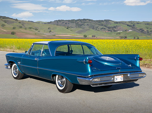 AUT 21 RK3335 01 © Kimball Stock 1957 Chrysler Imperial Crown Turquoise And White 3/4 Rear View On Pavement By Wildflowers And Hills