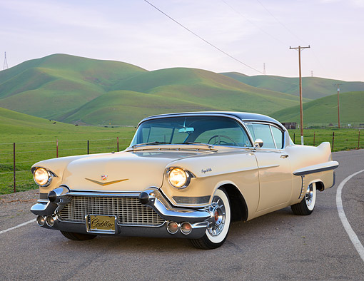 AUT 21 RK3344 01 © Kimball Stock 1957 Cadillac Coupe De Ville Beige 3/4 Front View On Road By Grassy Hills