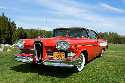 AUT 21 RK3363 01 © Kimball Stock 1958 Edsel Pacer Hardtop Convertible Red And White 3/4 Front View On Grass By Trees