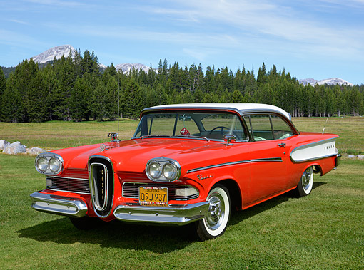 AUT 21 RK3364 01 © Kimball Stock 1958 Edsel Pacer Hardtop Convertible Red And White 3/4 Front View On Grass By Trees And Mountains