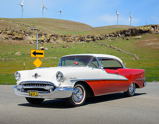 AUT 21 RK3365 01 © Kimball Stock 1955 Oldsmobile 98 Holiday 2-Door Hardtop Red And White 3/4 Front View On Pavement By Windmills