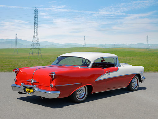 AUT 21 RK3366 01 © Kimball Stock 1955 Oldsmobile 98 Holiday 2-Door Hardtop Red And White 3/4 Rear View On Pavement By Field