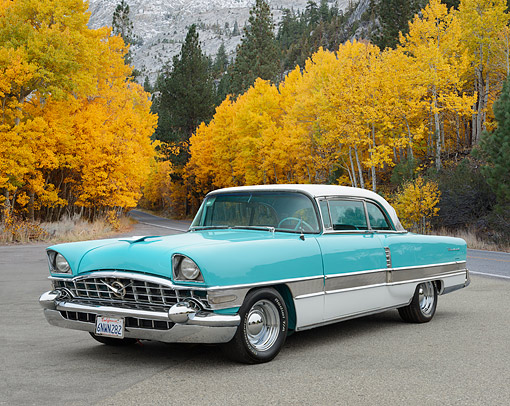 AUT 21 RK3368 01 © Kimball Stock 1956 Packard 400 Teal 3/4 Front View On Pavement By Autumn Trees