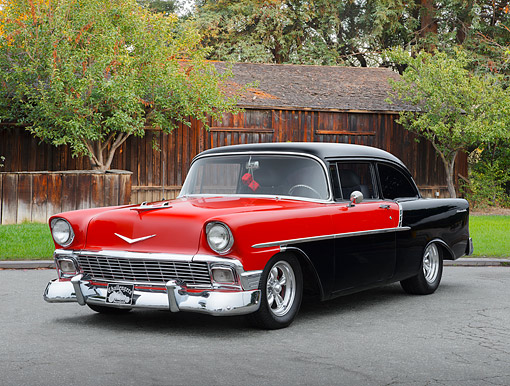 AUT 21 RK3373 01 © Kimball Stock 1956 Chevrolet 210 Red And Black 3/4 Front View On Pavement By Building