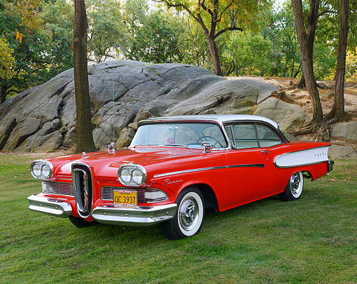 AUT 21 RK3379 01 © Kimball Stock 1958 Edsel Red 3/4 Front View On Grass By Rock And Trees