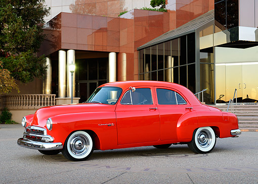 AUT 21 RK3389 01 © Kimball Stock 1951 Chevrolet Styleline Red 3/4 Side View On Pavement By Building