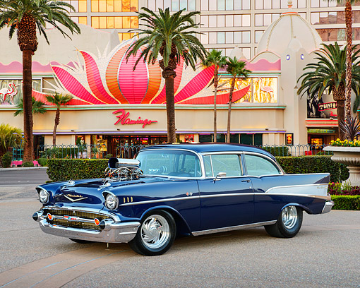 AUT 21 RK3393 01 © Kimball Stock 1957 Chevrolet Bel Air Blue 3/4 Front View On Pavement By Casino And Palm Trees