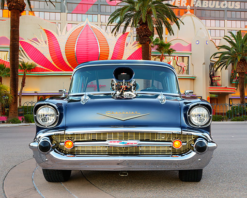 AUT 21 RK3394 01 © Kimball Stock 1957 Chevrolet Bel Air Blue Front View On Pavement By Casino And Palm Trees