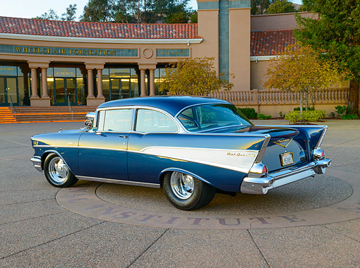 AUT 21 RK3395 01 © Kimball Stock 1957 Chevrolet Bel Air Blue 3/4 Rear View On Pavement By Building