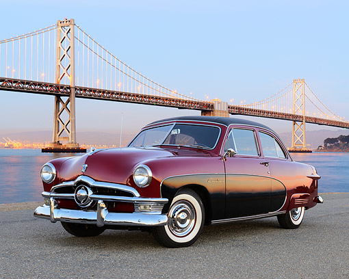 AUT 21 RK3398 01 © Kimball Stock 1950 Ford Crestliner Red And Black 3/4 Front View On Pavement By Bridge At Dusk