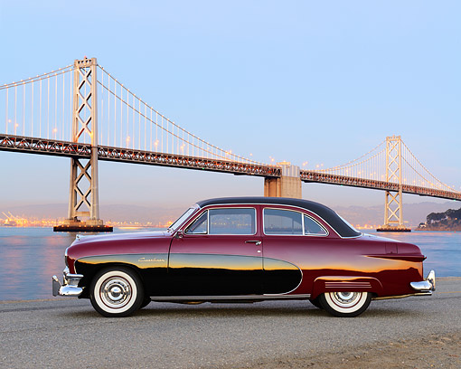 AUT 21 RK3399 01 © Kimball Stock 1950 Ford Crestliner Red And Black Profile View On Pavement By Bridge At Dusk