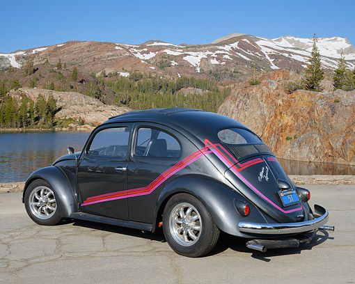 AUT 21 RK3401 01 © Kimball Stock 1957 Volkswagen Bug Oval Dark Charcoal Gray 3/4 Rear View On Pavement By Lake And Mountains