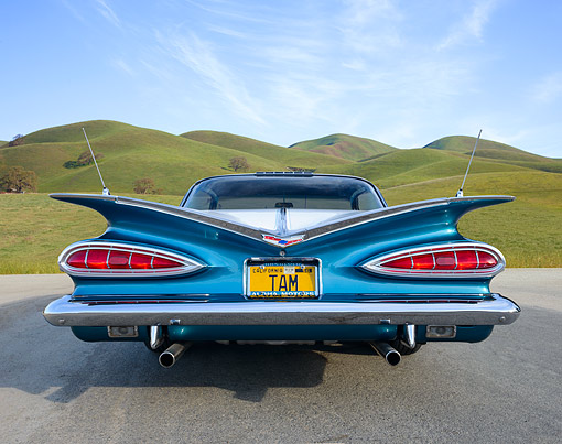 AUT 21 RK3404 01 © Kimball Stock 1959 Chevrolet Impala Teal And White Rear View On Pavement By Grassy Hills