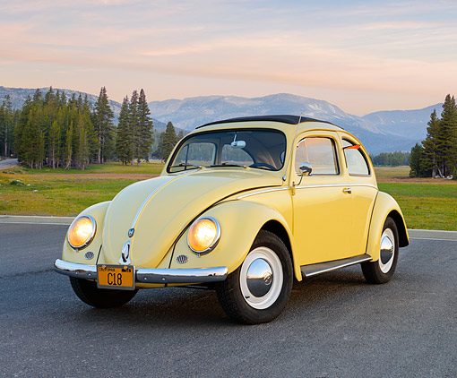 AUT 21 RK3406 01 © Kimball Stock 1959 Volkswagen Beetle Yellow 3/4 Front View On Pavement By Mountains At Dusk