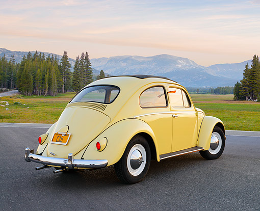 AUT 21 RK3407 01 © Kimball Stock 1959 Volkswagen Beetle Yellow 3/4 Rear View On Pavement By Mountains At Dusk