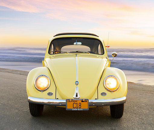 AUT 21 RK3408 01 © Kimball Stock 1959 Volkswagen Beetle Yellow Front View On Pavement By Beach At Sunset