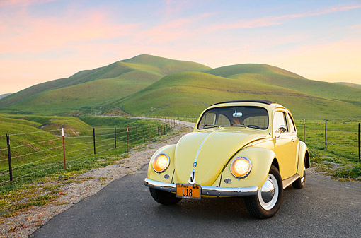 AUT 21 RK3409 01 © Kimball Stock 1959 Volkswagen Beetle Yellow 3/4 Front View On Road By Grassy Hills At Dusk