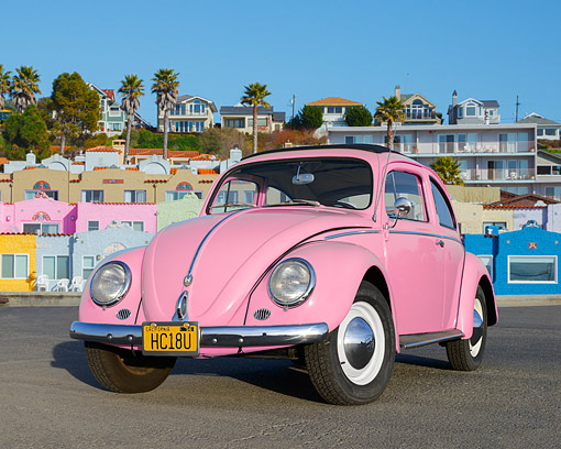 AUT 21 RK3410 01 © Kimball Stock 1959 Volkswagen Beetle Pink 3/4 Front View On Pavement By Colorful Houses