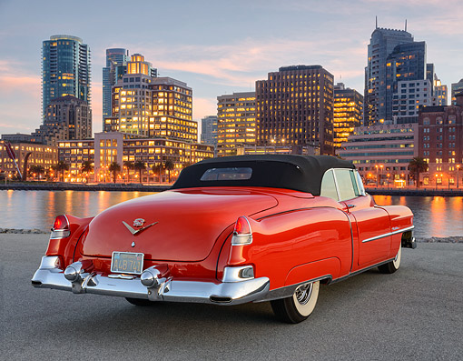 AUT 21 RK3420 01 © Kimball Stock 1953 Cadillac Eldorado Convertible Red 3/4 Rear View On Pavement By Skyscrapers At Dusk