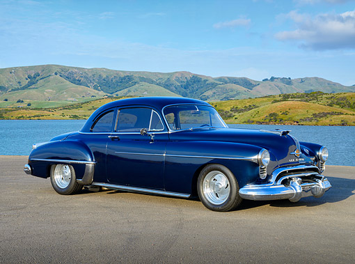 AUT 21 RK3422 01 © Kimball Stock 1950 Oldsmobile Club Coupe Dark Blue 3/4 Side View On Pavement By Water And Hills