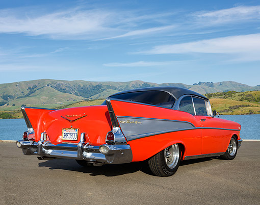AUT 21 RK3435 01 © Kimball Stock 1957 Chevrolet Bel Air Red With Gray Top 3/4 Rear View On Pavement By Water And Hills