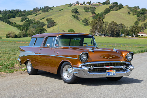 AUT 21 RK3439 01 © Kimball Stock 1957 Chevrolet Bel Air Nomad Chestnut 3/4 Front View On Pavement By Grassy Hills