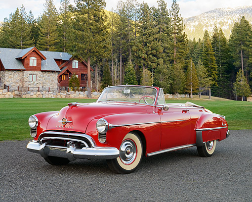 AUT 21 RK3575 01 © Kimball Stock 1950 Oldsmobile 88 Convertible Red 3/4 View On Pavement Near House