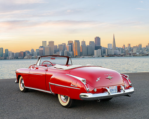 AUT 21 RK3576 01 © Kimball Stock 1950 Oldsmobile 88 Convertible Red 3/4 View On Pavement Against Cityscape