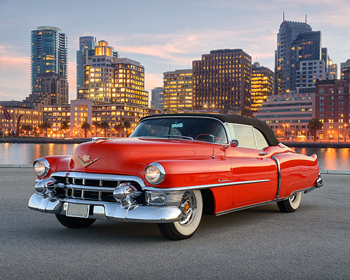 AUT 21 RK3585 01 © Kimball Stock 1953 Cadillac Eldorado Convertible Red 3/4 Front View On Pavement By Skyscapers At Dusk