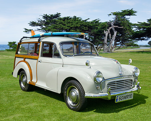 AUT 21 RK3606 01 © Kimball Stock 1957 Morris Minor White 3/4 Front View With Surfboard On Grass By Ocean
