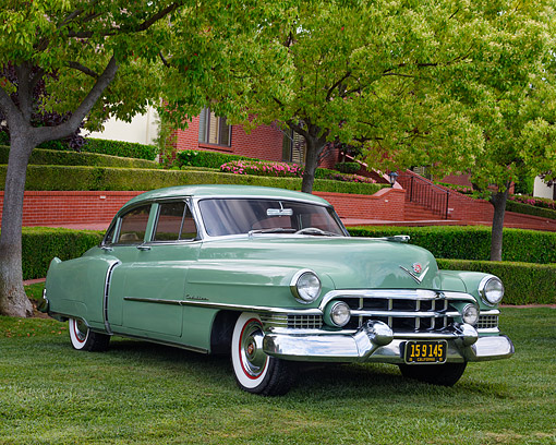 AUT 21 RK3612 01 © Kimball Stock 1951 Cadillac Sedan Green 3/4 Front View On Grass By Brick Building