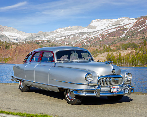 AUT 21 RK3639 01 © Kimball Stock 1951 Nash Ambassador Air Flyte Silver 3/4 Front View On Pavement By Lake And Mountains