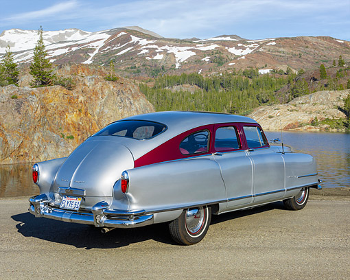 AUT 21 RK3640 01 © Kimball Stock 1951 Nash Ambassador Air Flyte Silver 3/4 Rear View On Pavement By Lake And Mountains